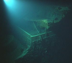 Researchers visiting deep wrecks need to bring everything – including their own light. In this haunting image, Titanic's bow is a stage for shadows and twisted steel. (Courtesy of NOAA/IFE/URI)